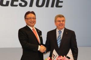 調印後握手を交わす津谷CEO(左)とバッハ会長