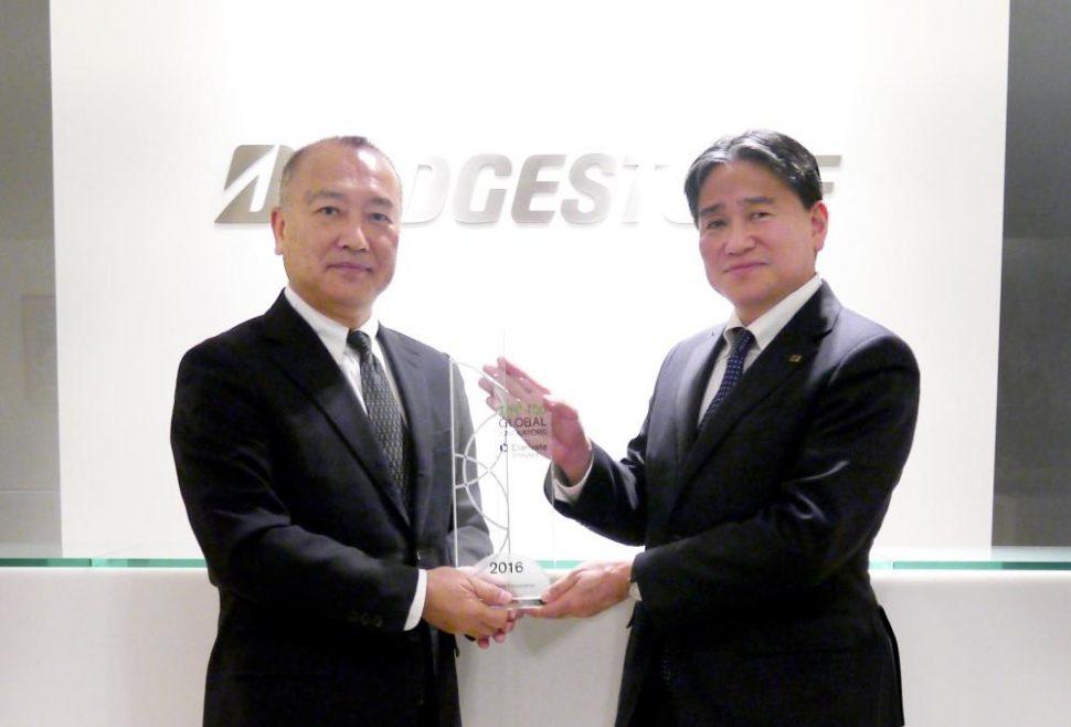 クラリベイト アナリティクの日野・日本代表(左)からトロフィーを授与されるれる荒木充・知的財産本部長